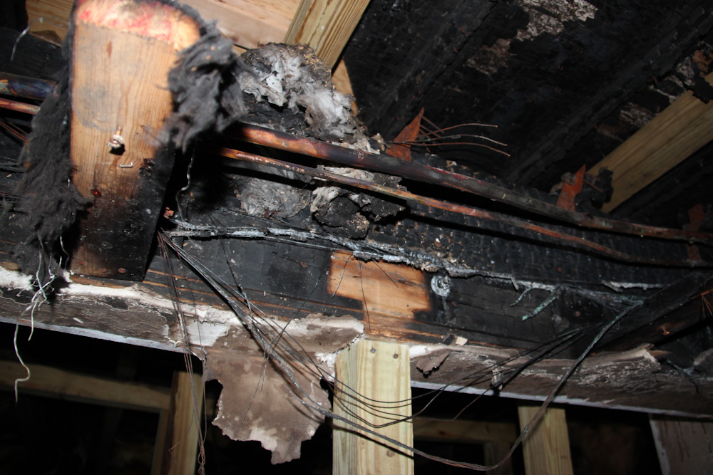 a burnt wooden beam and a torn down ceiling